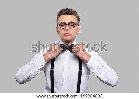 Confident in his skills. Serious young nerd man adjusting his bow tie and looking at camera while standing against grey background