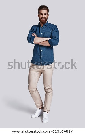 Confident in his style. Full length of handsome young man looking at camera and keeping arms crossed while standing against grey background #613564817
