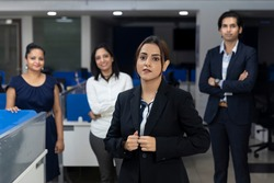 Confident Indian businesswoman standing infront of her office colleagues, selective focus, corporate environment, team members, business office.
