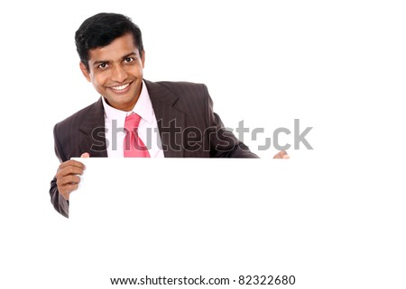 Confident Indian young businessman posing with white board