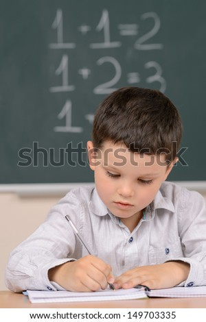 Confident little schoolboy. Confident little boy writing something in his note pad while sitting in front of the blackboard