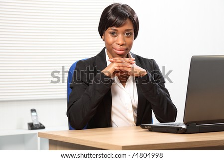 Confident looking young black business woman in office sitting to her desk resting her chin on folded hands.