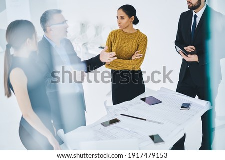Confident male and female business owners discussing trade exchange and management strategy for company, group of people in formal wear collaborating together during teamwork on blueprints in office Photo stock ©