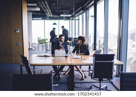 Confident male and female colleagues analyzing information during cooperation working process, formally dressed executive managers communicating about report during together business experience