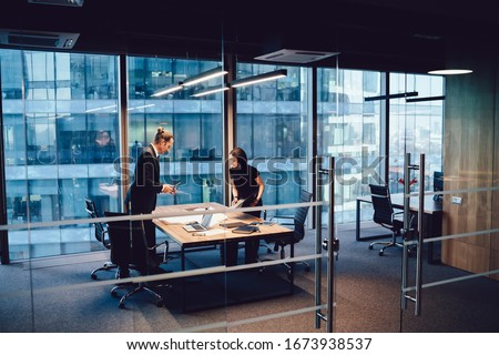 Confident male and female colleagues discussing project organization and planning looking at sketch on table together,prosperous employes in formal wear having meeting communication and analyzing
