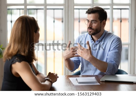 Confident male boss leader in eyeglasses explaining project details to new female employee at meeting. Concentrated young woman job applicant listening to hr manager questions at interview in office.