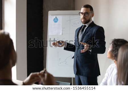 Confident male business trainer coach leader give flip chart presentation at office training, businessman conference speaker wear suit teach executive group explain strategy at corporate workshop