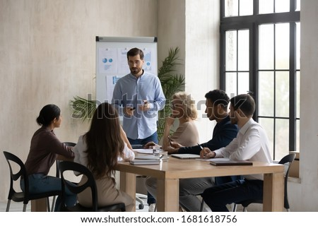 Confident male Caucasian team leader head meeting in office, present project on whiteboard, man speaker or coach talk make flip chart presentation to multiracial colleagues at briefing