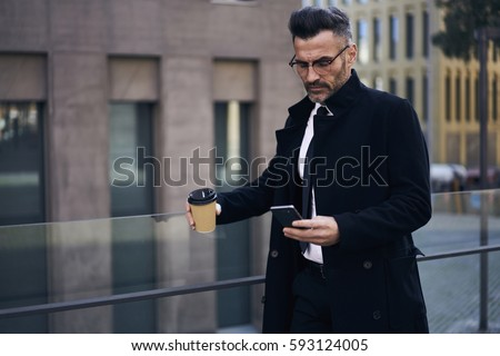 Confident male CEO supervising work of employees checking financial reports in online database via smartphone connected to fast 4G internet during work break standing outdoors with cup of coffee