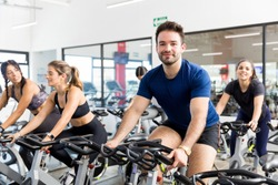 Confident male client smiling while exercising on bike with friends in gym