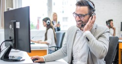 Confident male customer support operator with headset working in call center