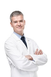 Confident male doctor or pharmacist in white lab coat standing with folded arms smiling at the camera isolated on white