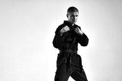 Confident male in kimono fighter posing in karate stance on studio background with copy space, black and white portrait