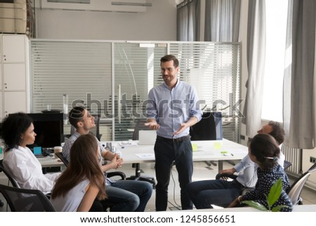 Confident male leader, coach holding briefing for multiracial team employees in office, discussing, explaining business strategy, plan to subordinates, businessman at company meeting with colleagues
