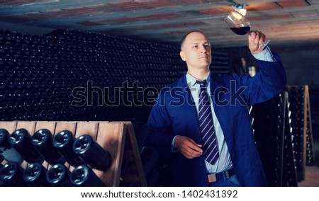Confident male winemaker degusting red wine in wine cellar near bottles racks  Foto stock ©