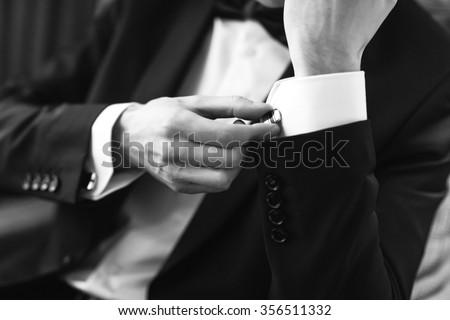Confident man buttons cufflinks. Cufflinks closeup. Men\'s suit, tuxedo.