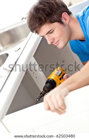 Confident man holding a drill repairing a kitchen sink at home - stock photo