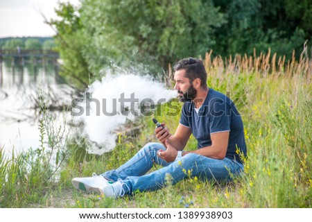 Confident man in the fresh air smoking an electronic cigarette. Electronic cigarette. #1389938903