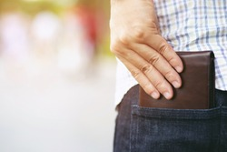 Confident man posing in safe keeping your wallet in the back pocket of his back pocket pants. savings money finance.
