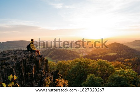 Confident man sitting on the edge. Amazing view  in hilly landscape far from people. Tourist student is relaxing in nature during sunset. Traveling sitting in mountains. Adventure, Art, Travel and Hike concept.
