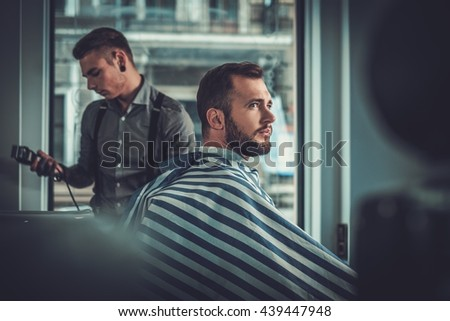 Confident man visiting hairstylist in barber shop. #439447948