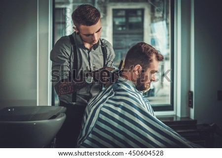 Confident man visiting hairstylist in barber shop. #450604528