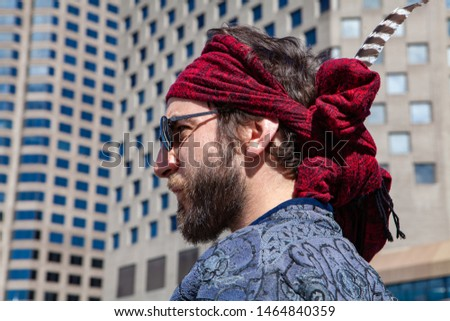 Confident man wears red bandanna in city. A closeup side profile of a young bearded Caucasian male standing downtown wearing bohemian style clothing. Sacred person contemplates urban surroundings. #1464840359