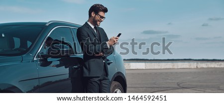 Confident manager. Full length of handsome young businessman using smart phone while standing near his car outdoors