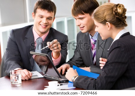 Confident manager is explaining the correct way of analysis to his colleagues in  the office pointing at the monitor