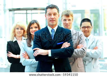 Confident mature business man with colleagues at the background