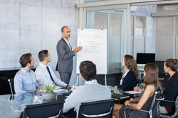 Confident mature businessman giving a presentation to his team in office. Business brief with annual goals with employees. Leadership man training businessmen and businesswomen in conference room.