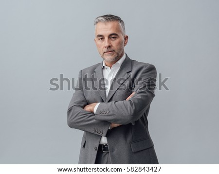 Confident mature businessman posing with arms crossed and looking at camera #582843427