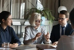Confident mature businesswoman mentor team leader in glasses speaking, training, leading corporate meeting with diverse employees, colleagues business partners talking negotiating at briefing