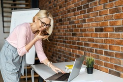 Confident middle aged businesswoman in glasses using voice recognition function on a smartphone. Modern female entrepreneur looking at the laptop, sending a vocal message via online messenger