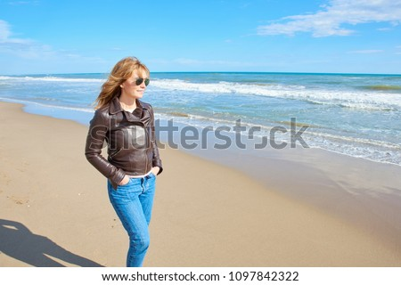 Confident middle aged woman  (wearing jeans, leather jacket and sunglasses) walking on the beach and enjoying beach air. #1097842322