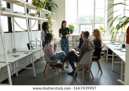 Confident millennial businesswoman stand lead multiracial team meeting in modern coworking office, successful female leader talk brainstorm with diverse colleagues, cooperate at briefing at workplace
