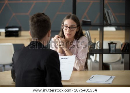 Confident millennial female applicant talking at job interview answering questions, young serious candidate speaking to hr telling about work experience, introduction and first impression concept
