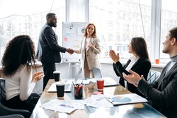 Confident multiethnic business people are shaking hands on briefing meeting in modern office. Successful business teams coming to agreetment after negotiations, coworking concept