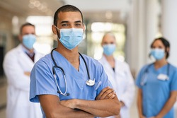 Confident multiethnic male nurse in front of his medical team looking at camera wearing face mask during covid-19 outbreak. Happy and proud indian young surgeon standing in front of his colleagues.