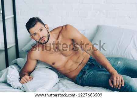 confident muscular man in jeans laying in bedroom at home