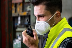 Confident of engineer or manager worker wearing a mask and using walkie-talkie and talk to other staff. Working at manufacturing, plant, factory. Feeling tired, more sweat on face. COVID concept
