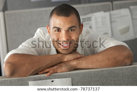 Confident office worker rests his chin on his arms
