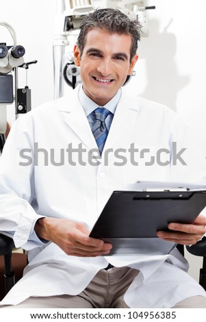 Confident optometrist smiling while holding a clipboard at his clinic