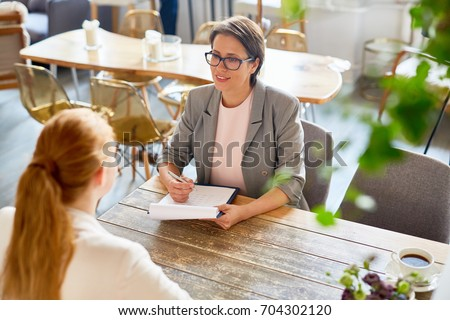 Confident owner of cafe interviewing young specialist