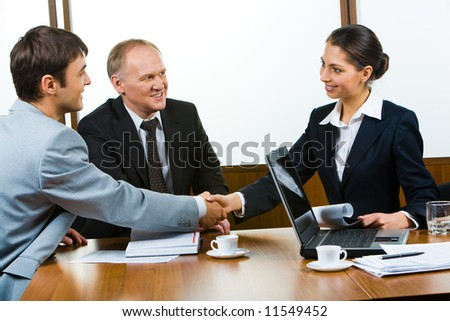 Confident partners sitting at the table and shaking hands