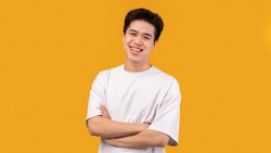Confident Person. Portrait of smiling asian guy with folded arms looking at camera, wearing white shirt, posing isolated over orange studio background. Happy casual male teenage model laughing