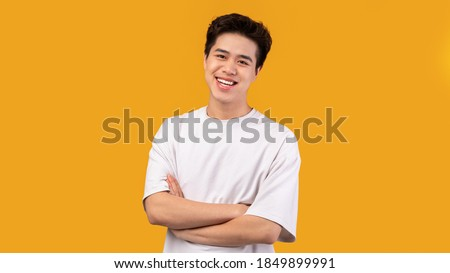 Confident Person. Portrait of smiling asian guy with folded arms looking at camera, wearing white shirt, posing isolated over orange studio background. Happy casual male teenage model laughing Stockfoto ©