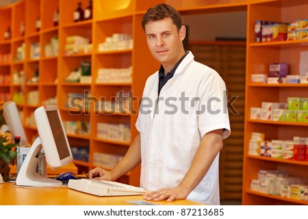 Confident pharmacist standing behind counter in a pharmacy - stock photo