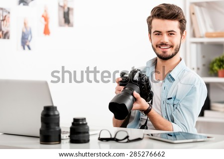 COnfident photographer. Cheerful young man holding digital camera and smiling while sitting at his working place
