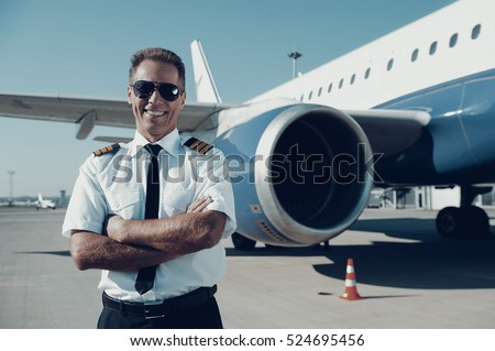 Confident pilot. Confident male pilot in uniform keeping arms crossed and smiling with airplane in the background